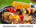 Small photo of Vegetarian or vegan kebabs with tofu on the barbecue grilling over a hot fire outdoors with tomatoes and corn on the cob