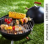 Small photo of Halloumi or tofu vegetarian kebabs grilling on an outdoor portable BBQ with corn on the cob on a green lawn in a concept of healthy outdoors summer lifestyle and vegan or vegetarian cuisine