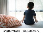 Small photo of The Problem of Child Development:A little boy sitting by the bed looking through the window Absent-minded. Recognizing Developmental Delays in Children, Autism awareness, Psychological trauma.