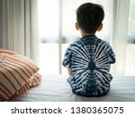 Small photo of The Problem of Child Development:A little boy sitting by the bed looking through the window Absent-minded. Recognizing Developmental Delays in Children, Autism awareness, Psychological trauma Kids.