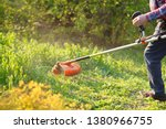 Man Mows The Lawn Grass With A...