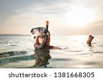 Small photo of Caucasian man snorkeling, floating on the surface, spitting out water with a funny goofy facial expression, summer seaside vacation activity