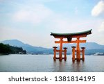 Stock photo itsukushima shinto torii on the water with the city and mountains behind miyajima island japan 1381814195