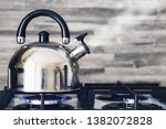 A Metal Silver Teapot On A Gas...