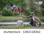 Porvoo, Finland - June, 2019: The people of Finland, a beautiful couple having picnic and enjoying a sunny day in Porvoo village.