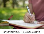 Stock photo poem poetry and knowledge education concept close up sitting writing on notebook in park 1382178845