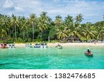 Small photo of Tropical beach with boats on an unsettled island near Phu Quoc, Vietnam