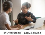 Small photo of Excited multiethnic female employees discuss work issues sitting at office table, smiling diverse women workers or colleagues engaged in brainstorming talk chatting, explain ideas at workplace