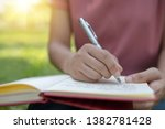 Stock photo poem poetry and knowledge education concept close up sitting writing on notebook in park 1382781428