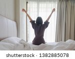 Stock photo woman stretching in bed after waking up back view woman sitting near the big white window while 1382885078