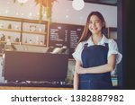 Stock photo pretty young asian waitress standing arms crossed in cafeteria coffee business owner concept 1382887982