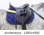 A saddle saddled on the back of a sport horse - stock photo