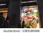Small photo of Ho Chi Minh City, Vietnam - April 23, 2019: Dolce & Gabbana shop's exterior with people passing by in the night street, on a motorbike and afoot.