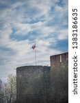 View from Estonian side over the river Narva to the Russian flag on the top of the watch tower of the medieval castle Ivangorod Fortress (Leningrad Oblast, Russia).