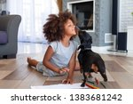 Stock photo funny little african american girl lying on floor coloring picture having fun with dog family pet 1383681242