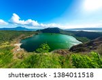 Small photo of View of cones of Taal Volcano and the wind ruffled emerald green water in the Lake Taal on a sunny day in Tagaytay, Philippines.