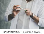 male dentist with tooth model... | Shutterstock . vector #1384144628