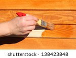 hand with paintbrush on wood | Shutterstock . vector #138423848