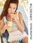 happy girl is drinking fruit...   Shutterstock . vector #1384282718