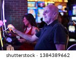 elderly tourist playing slot... | Shutterstock . vector #1384389662