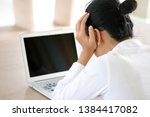 Small photo of woman sitting down, his face unsettled. At the computer desk she has headaches and stress. Cause of hard work and insufficient rest