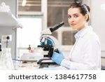 Content young lady with hair bun wearing lab coat and rubber gloves sitting at table and looking at camera while studying bacteria in laboratory