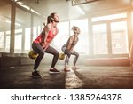 Two Woman Lifting Kettle Bell...
