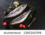 Stock photo marinated mackerel or herring fish with spices greens and onion on slate stone background 1385265398