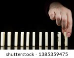 female hand sets dominoes in a... | Shutterstock . vector #1385359475