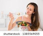 woman eating an appetizing... | Shutterstock . vector #1385569055