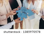 businesspeople joining puzzle... | Shutterstock . vector #1385970578