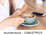 woman in a cafe drinking coffee ... | Shutterstock . vector #1386379925