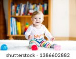 adorable baby girl playing with ... | Shutterstock . vector #1386602882