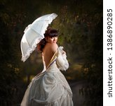 Small photo of Beautiful woman in vintage dress with a white umbrella on the background of greenery. Selective focus. Gallant century.
