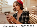 Small photo of Winsome elegant girl texting message in autumn day. Debonair short-haired woman in red beret standing on the street with phone.