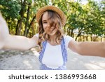 Stock photo european cute girl with wavy hair playfully posing in park emchanting lady in hat making selfie 1386993668