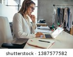 businesswoman sitting at her... | Shutterstock . vector #1387577582
