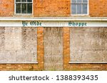 """Boarded up village shop with a sign saying """"Ye Olde Country Shoppe"""""""