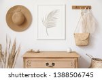 Small photo of Stylish korean interior of living room with brown mock up poster frame, elegant accessories, flowers, wooden shelf and hanging rattan bags and hat. Minimalistic concept of home decor. Template.