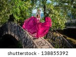 Romantic portrait of the woman in airy crimson dress dancing on the bridge, sea view on background - stock photo