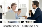 Small photo of Concentrated man and woman workers sit at office desk negotiating using laptop discussing ideas, diverse colleagues talk brainstorming negotiate on business project together. Cooperation concept