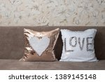 Small photo of Pillows with sequins. White and golden pillows lie on a brown sofa. Golden pillow with a white heart, white pillow with the inscription Love. Place for text