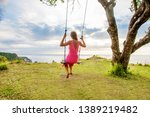 woman swinging on a swing on a... | Shutterstock . vector #1389219482