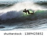 Surfer in Hossegor riding waves. Shot was taken in France, showing a silhouette of a surfer man on his shortboard.