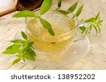 Small photo of Lemon verbena Herbal Tea in a glass cup. Aloysia citriodora. Naturopathy. White Background. Focus on foreground.