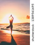 Small photo of Yoga wellness retreat class on morning sunrise beach landscape. Silhouette of girl standing in tree pose meditation vertical background.