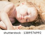 small child sunbathes on hot... | Shutterstock . vector #1389576992