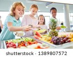 Stock photo hungry children as students pick up fruit at the cafeteria s buffet 1389807572