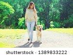 Stock photo woman owner walking with her golden retriever dog on leash in summer day 1389833222