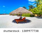 wooden sunbed and umbrella on... | Shutterstock . vector #1389977738